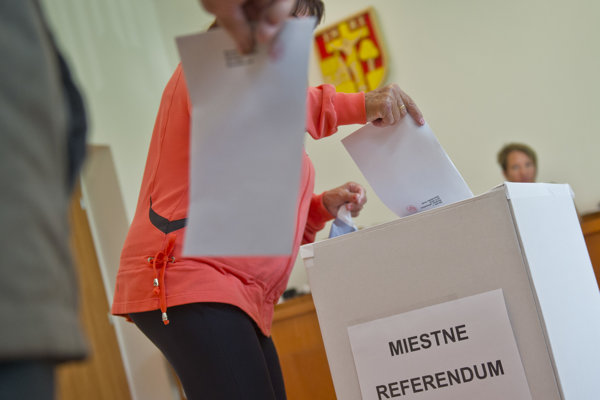 Občania vhadzujú obálky do urny počas miestneho referenda o odvolaní súčasného starostu obce Radovana Benčíka.