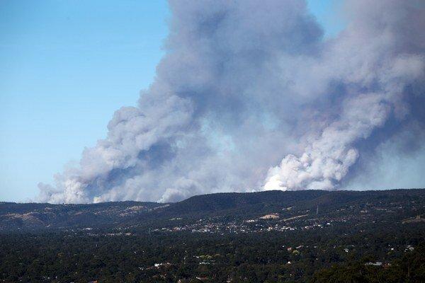 Dym z požiaru, ktorý zničil tucty domov.