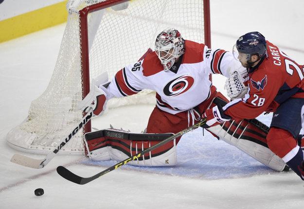 Hráč Washingtonu Capitals Paul Carey (vpravo) sa dostáva do šance pred brankárom Caroliny Hurricanes Alexom Nedeljkovicom.