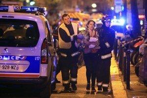 Záchranári pomáhajú žene po streľbe v koncertnej sieni Bataclan 13. novembra 2015 v Paríži.