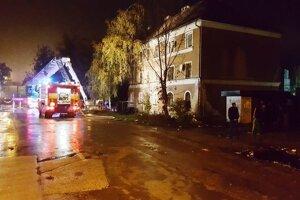 Dvadsať hasičov bojovalo v noci s požiarom strechy bytového domu.