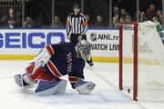 Brankár New Yorku Rangers Henrik Lundqvist vyťahuje zo svojej siete puk po rýchlom góle Bostonu Bruins.