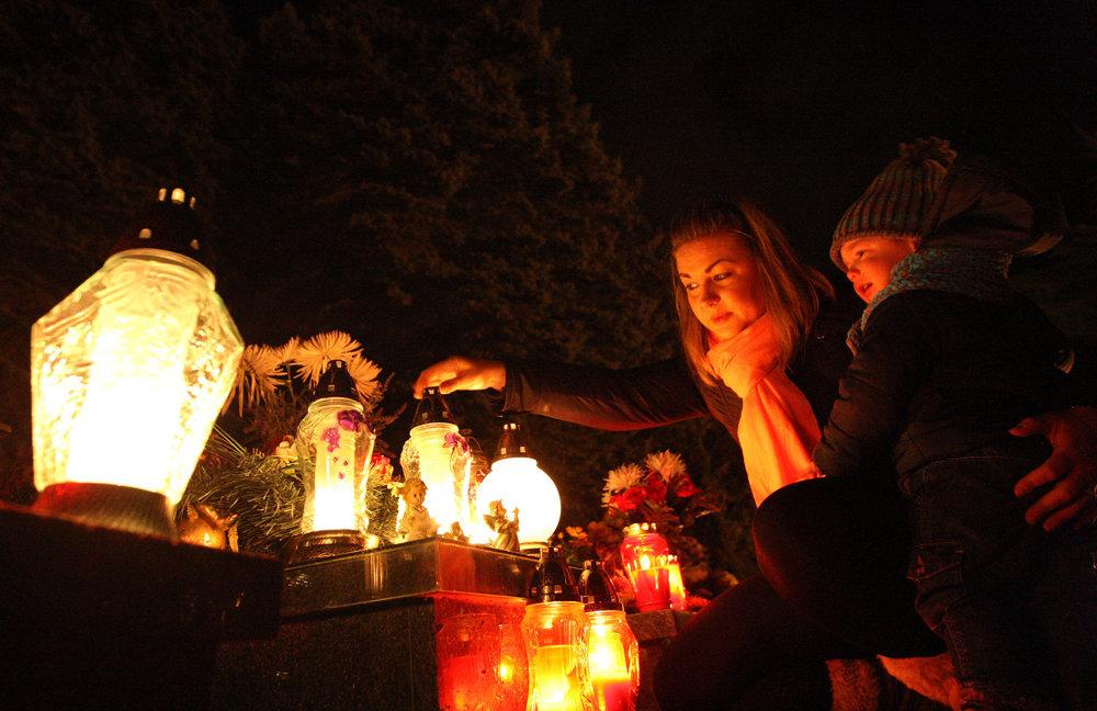 Zapaľovanie sviečok na cintoríne vo Zvolene