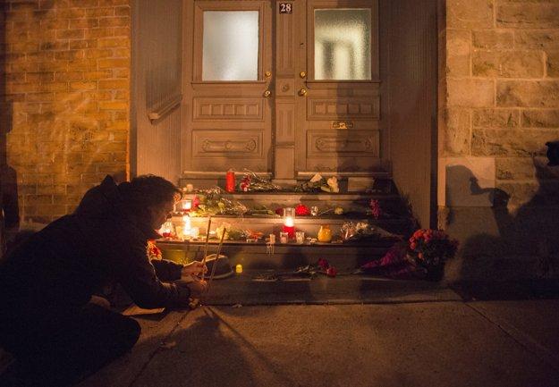 Ľudia pred Cohenovým domom v Montreale zapaľujú sviečky.