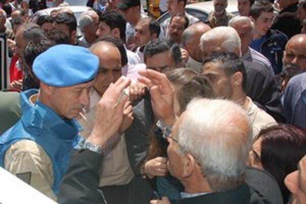Pozorovateľ mierových síl OSN (vľavo) sa rozpráva so Sýrčanmi počas návštevy v sýrskom meste Homs.