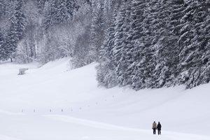 Ľudia počas prechádzky zasneženou krajinou v rakúskom Werfenwengu.