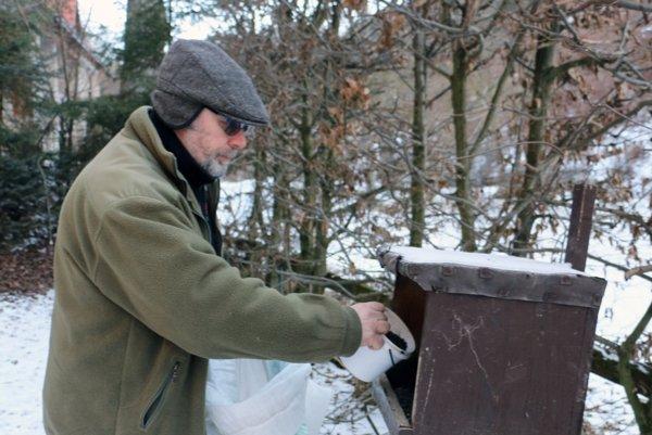Vladimír Slobodník pridáva slnečnicu do kŕmidla pre vtáky.