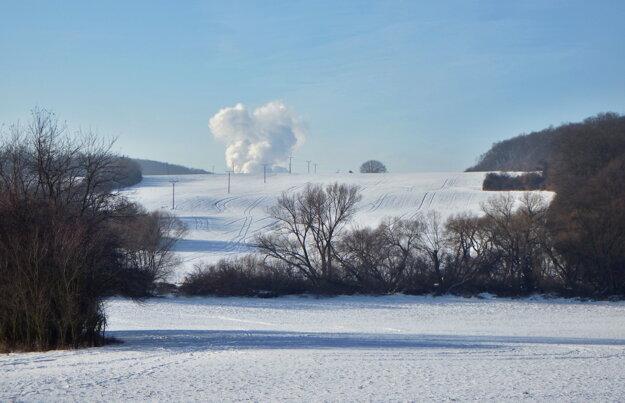Krajina je pod snehom. V pozadí sú mochovské veže.
