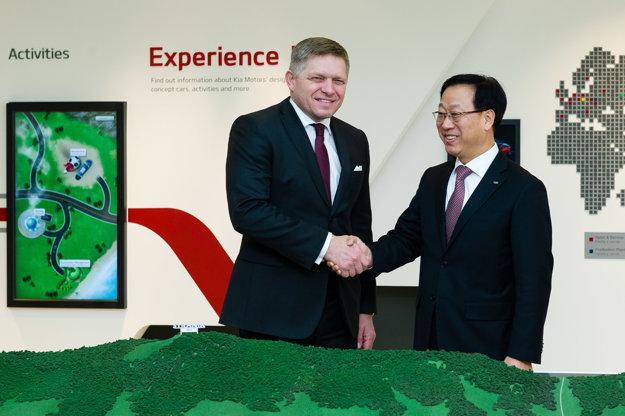 Predseda vlády SR Robert Fico (vľavo) a nový prezident Kia Motors Slovakia Dae Sik Kim (vpravo) pózujú po stretnutí s vedením spoločnosti vo výrobnom závode KIA.
