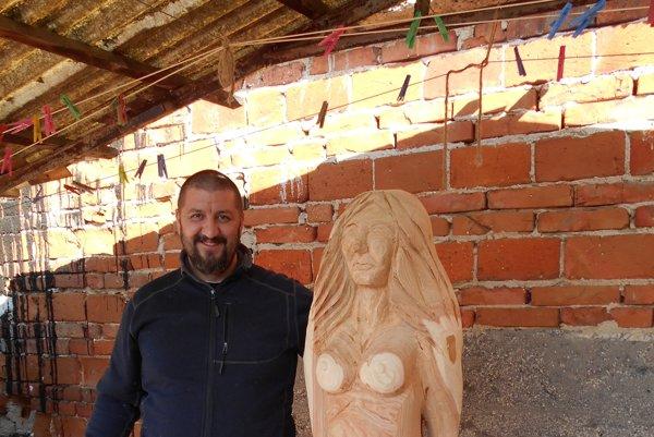 Rezbár Jozef Miklo vedľa jednej zo svojich sôch.