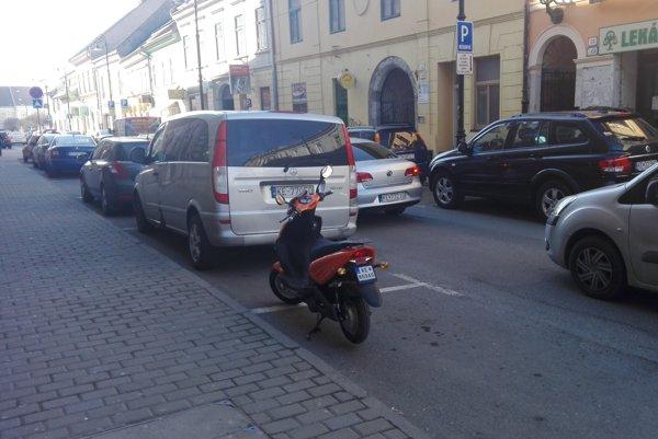 Motorka na Mäsiarskej. Pokiaľ by majiteľ tohto motocykla zaparkoval opol metra ďalej, na chodníku, nemusel uhradiť poplatok za parkovné.