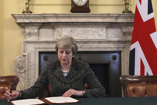 Theresa Mayová pri podpise listu.