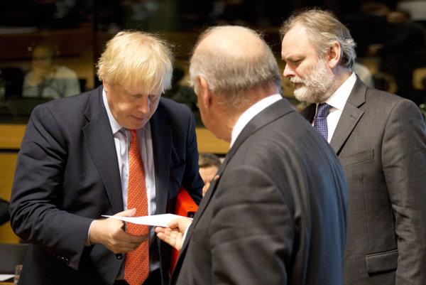 Britský šéf diplomacie Boris Johnson si berie obálku od maltského rezortného kolegu Georgea Vellu (uprostred) počas zasadnutia v Luxemburgu.