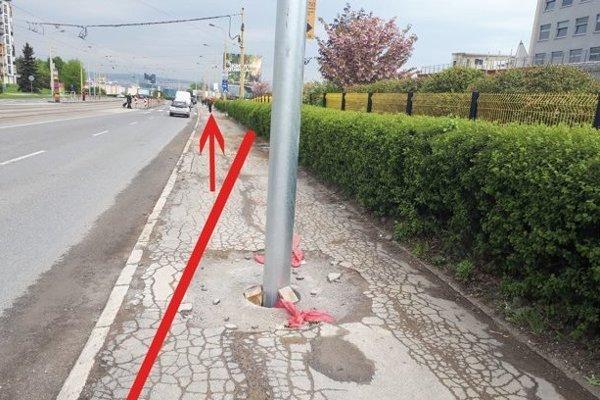 """Chodník na Moldavskej ceste. Stĺp už nebude v strede, lebo chodník """"odbočí"""" do živého plota. Bude musieť ustúpiť posunutej ceste (šipka vyznačuje, kde bude namiesto chodníka cesta)."""