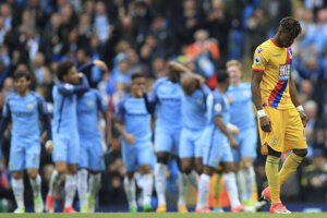 Futbalisti Manchesteru City oslavujú jeden zo svojich gólov do siete Crystal Palace, v popredí smúti Wilfried Zaha.
