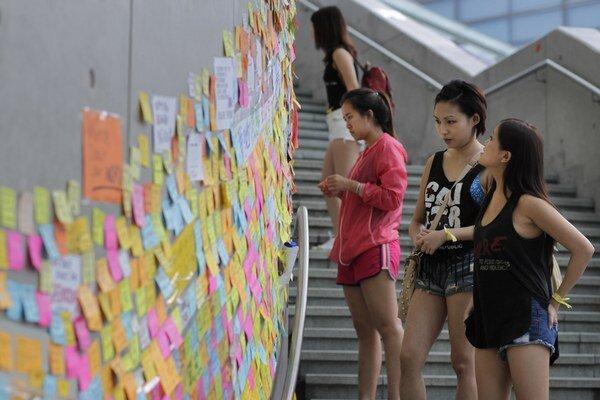 Študentky si čítajú odkazy na vládnej budove.