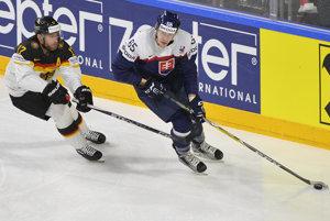 Slovenský obranca Michal Čajkovský (vpravo) korčuľuje s pukom na hokejke, bráni ho Nemec Marcus Kink.