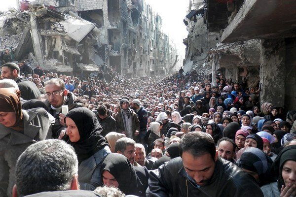 Symbolom sýrskeho zúfalstva je fotografia z tábora Jarmúk v Damasku, kde pri zničených budovách čakajú tisíce palestínskych utečencov  na pomoc.