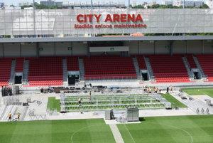 Prekrývanie trávnika a výstavba pódia na štadióne.