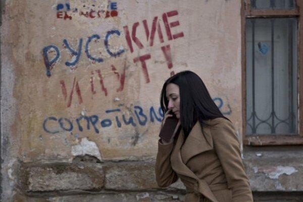 """Žena prechádza okolo nápisu, ktorý v ruštine znamená """"Rusi idú""""."""