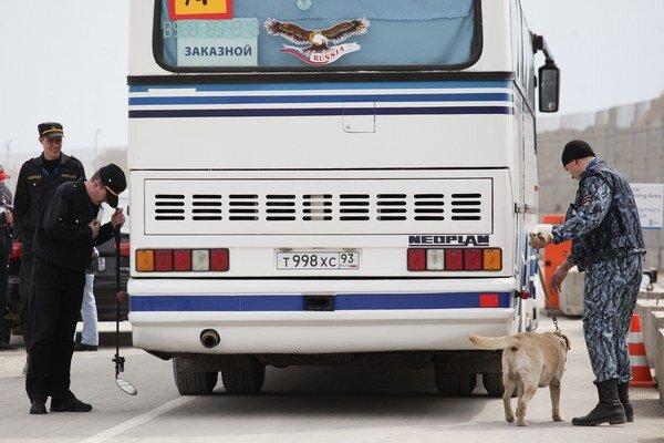 Policajti so psom kontrolujú autobus pred vstupom do Soči.
