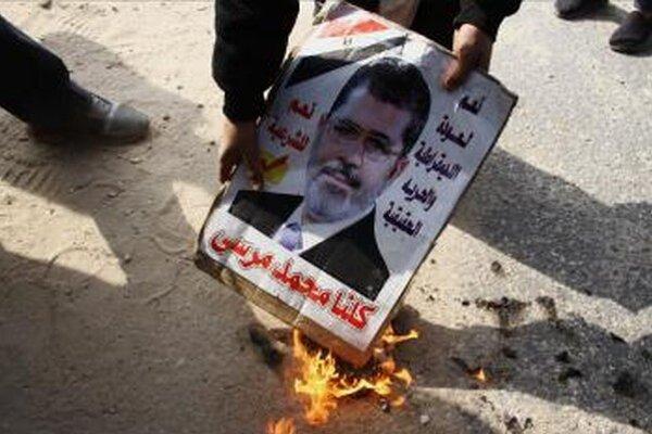 Odporca zosadeného egyptského islamistického prezidenta Muhammada Mursího zapaľuje jeho portrét počas protestu v Káhire.