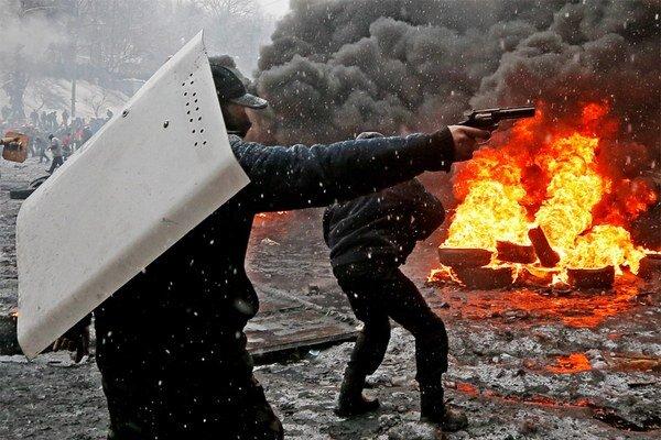 Demonštrant so zbraňou v ruke.