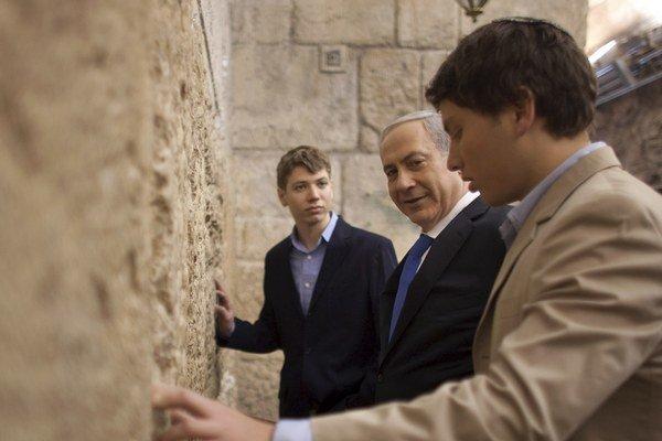 Syn premiéra (v pozadí).
