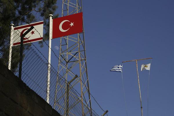 V popredí turecká zástava (vpravo) a zástava cyperských Turkov (vľavo). V pozadí je zasa vľavo grécka zástava a v pozadí vpravo cyperská zástava vejú v opustenej vojenskej základni v rozdelenej metropole Nikóza.