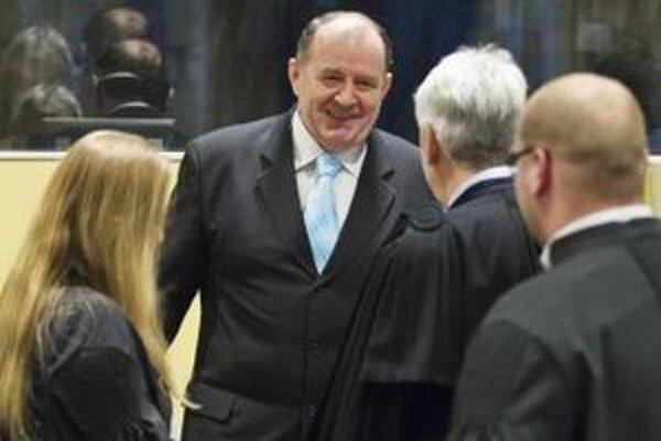 Bývalý bosnianskosrbský minister vnútra a národnej polície Mičo Stanišič (v strede) sa rozpráva so svojimi advokátmi pred začiatkom procesu v holandskom Haagu.