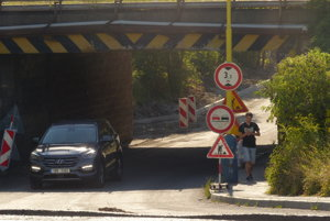 Chodci prebehujú cez obnovovaný úsek cesty na druhú stranu.