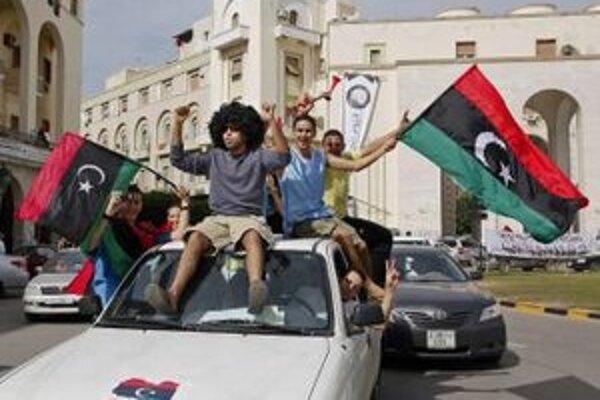 Líbyjčania oslavujú s revolučnými zástavami zabitie bývalého líbyjského vodcu Muammara Kaddáfího.