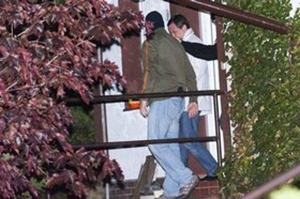 David Rath v sprievode policajtov odchádza zo svojho domu v Hostivici.
