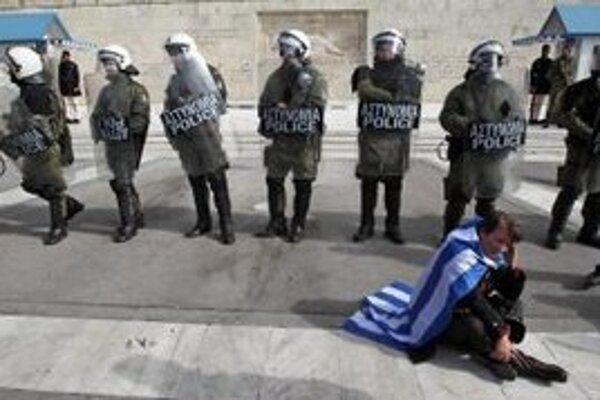 Demonštrant zahalený v gréckej zástave sedí pred kordónom policajtov pred gréckym parlamentom v Aténach.