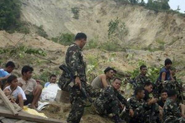 Filipínski záchranári a obyvatelia počas prestávky pri pátraní po nezvestných.
