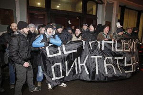 "Demonštranti držia transparent s nápisom ""Zastavme diktatúru""."