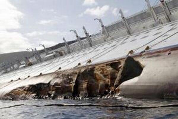 Skala útesu trčí z poškodeného trupu potopenej výletnej lode Costa Concordia.