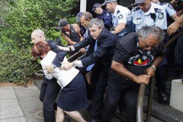 Austrálsku premiérku Juliu Gillardovú (vľavo) odvádzajú ochrankár a policajti do bezpečia.