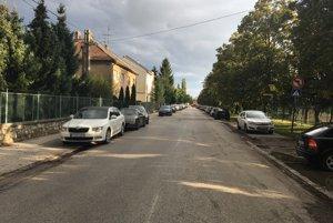Parkujúce autá lemujú obe strany ulice.