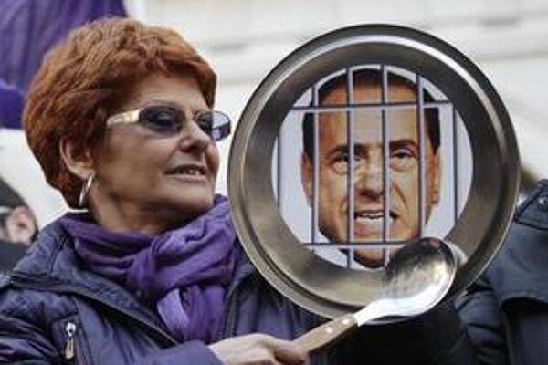 Žena udiera lyžicou o panvicu s portrétom premiéra Silvia Berlusconiho.