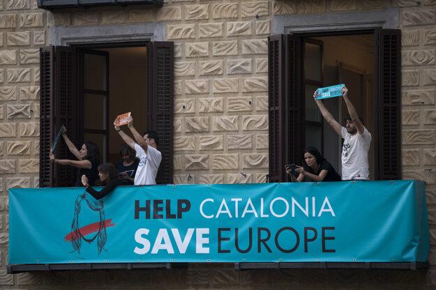 Ľudia držia plagáty na balkóne blízko vládnej budovy v centre Barcelony.