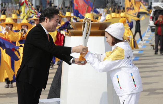 Juhokórejský predseda vlády Lee Nak-yon (vľavo) predáva pochodeň prvej nosičke - krasokorčulairke You Young.