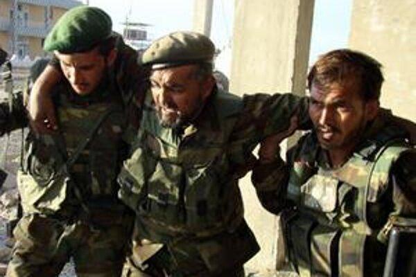 Afganskí vojaci pomáhajú zranenému spolubojovníkovi pri evakuácii do bezpečia počas prudkej prestrelky s bojovníkmi Talibanu v provincii Hilmand.