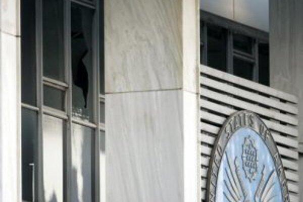 Rozbité okno pri embléme americkej ambasády v Aténach.