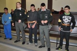 Trojica obvinených pred súdom s eskortou.