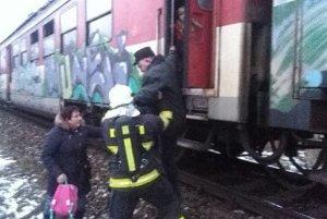Hasiči pomáhajú cestujúcim vo vlaku.