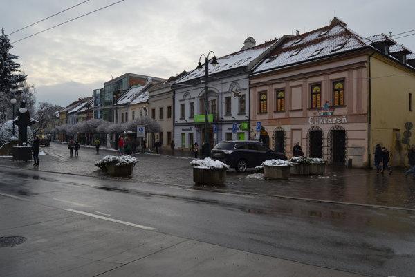 Na Trojici mesto osadilo 5 kvetináčov, za nimi sa nachádza parkovisko pre taxikárov.