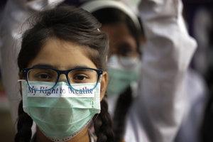 snímke indická školáčka s rúškom na tvári počas protestu proti znečistenému ovzdušiu v indickej metropole Naí Dillí 15. novembra 2017.