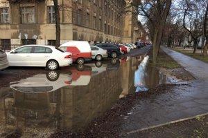 Obrovská kaluž. Okrem vozovky zaplavuje aj zeleň a chodník, ktoré boli revitalizované v rámci EHMK.