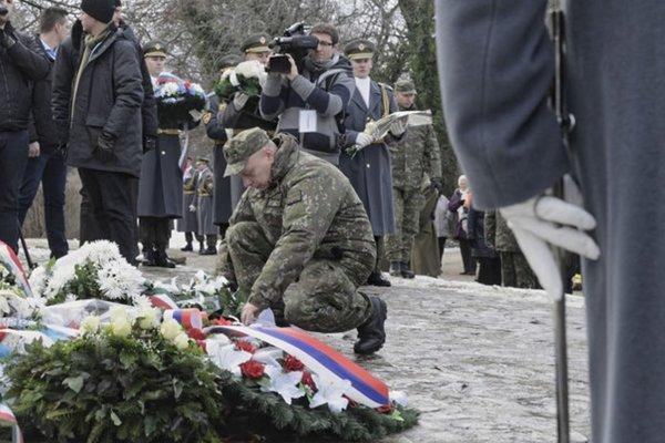 Jediný preživší Martin Farkaš (uprostred) kladie veniec pri pomníku obetiam v maďarskej obci Hejce.